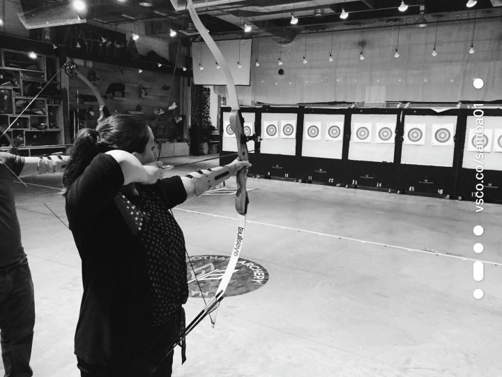 Woman draws a bow backward ready to shoot an arrow at a target during archery lesson at Gotham Archery in Brooklyn