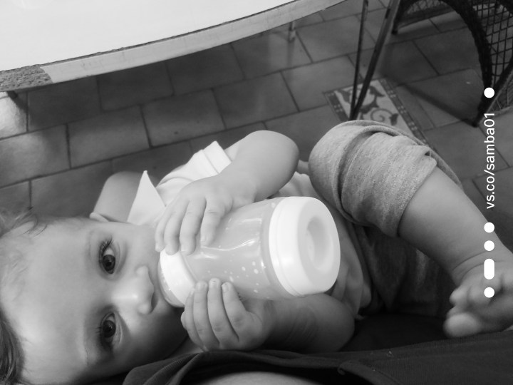 A black and white photograph of a baby drinking a bottle.