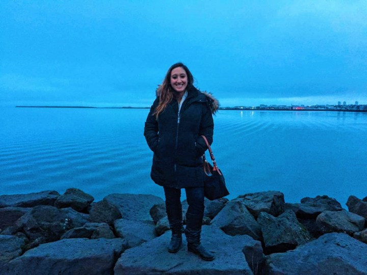 A woman in a winter coat standing by the water on a pile of rocks in Reykjavik, Iceland.