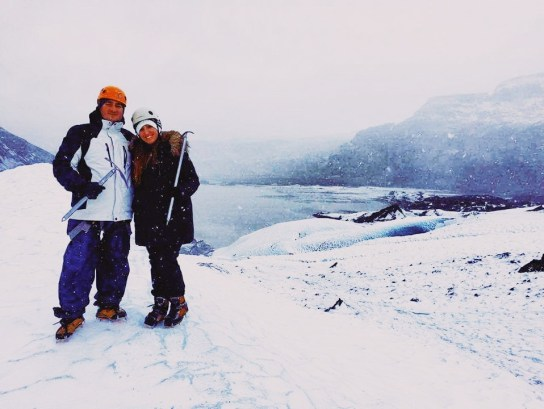 A couple poses for a picture as they climb Solheimajokull in Iceland