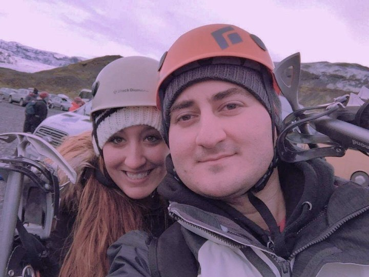 A couple wearing helmets takes a selfie before climbing Solheimajokull in Iceland