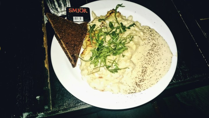 Thick, Icelandic fish chowder served on a plate instead of a bowl with a side of brown bread.