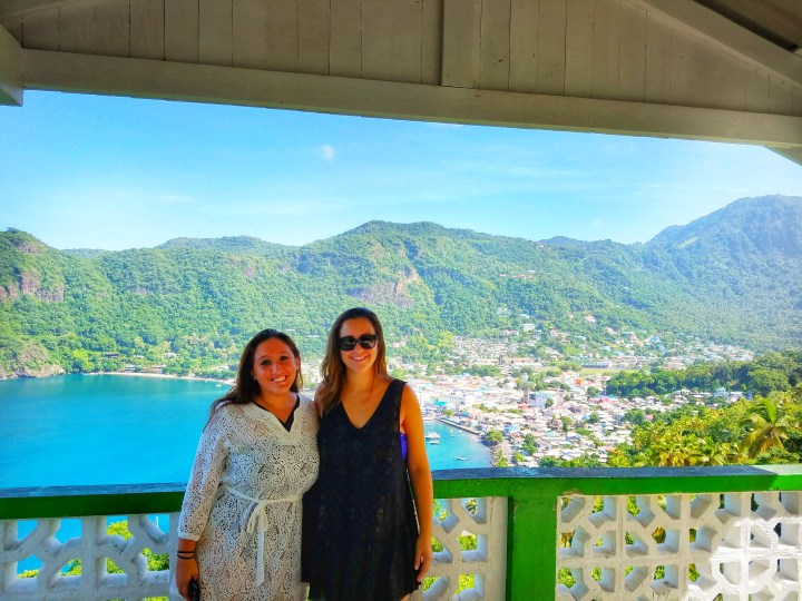 Two girls stand smiling at the camera with mountains, a bay, and colorful houses in the background during a one day trip to Soufriere