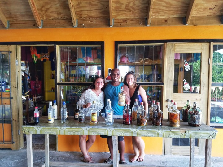 Two women stand on either side of a rum procurer during their one day trip to Soufriere.