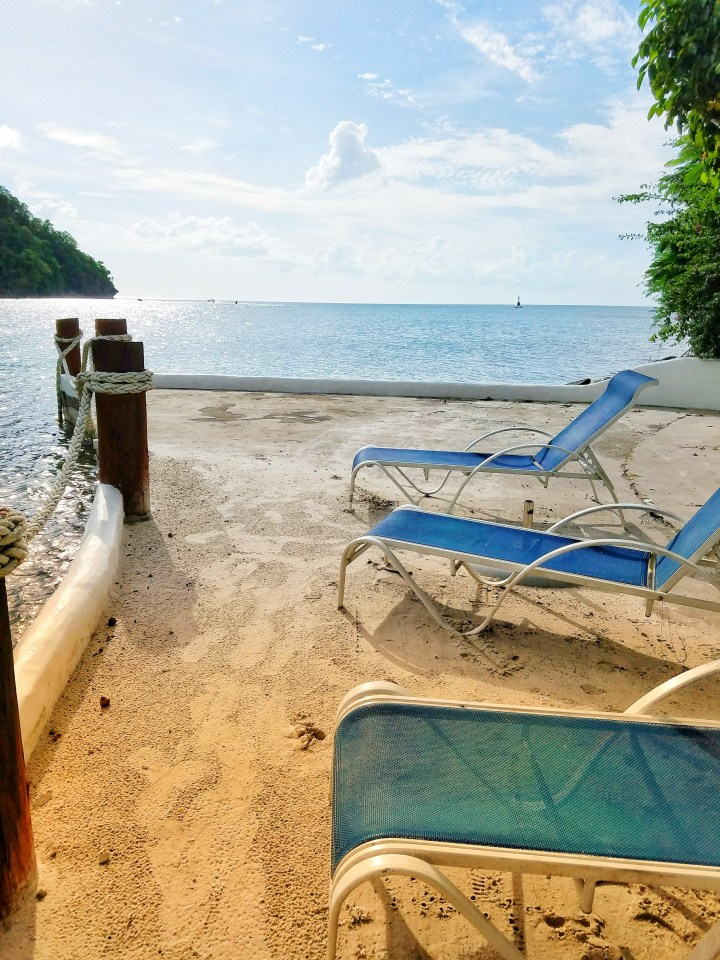 Three blue lounge chairs in the sand overlooking Marigot Bay. This was the perfect place to have many girl chats on my trip to St Lucia with a friend.