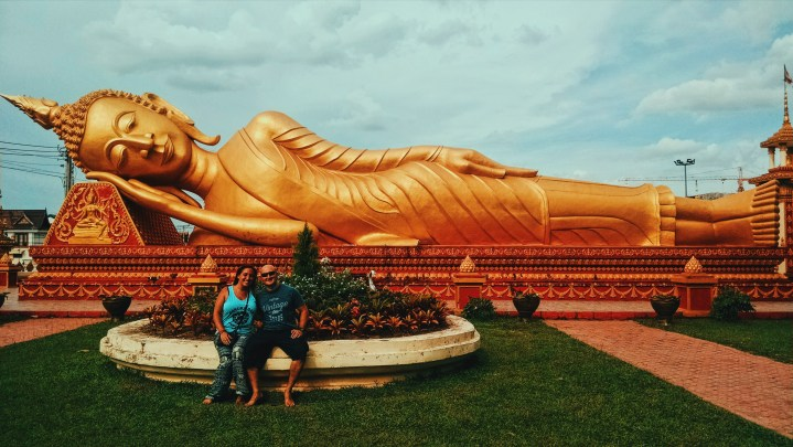 "A giant golden reclining, or ""sleeping"" Buddha outside of a temple in Vientiane, Laos. A couple poses in front of it, sitting on a bench."