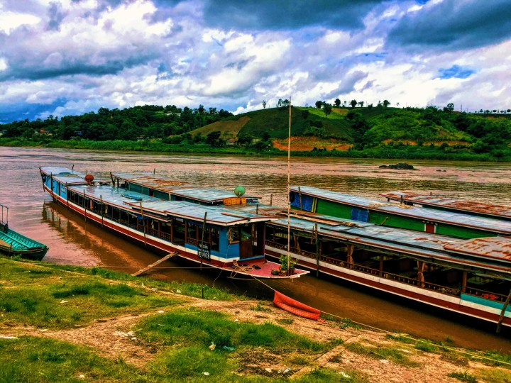 Three long slow boats pulled into port in Laos from the Mekong River
