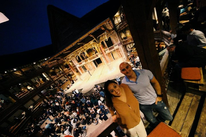A couple poses for a picture in the gallery of the Globe Theater. The woman has long brown hair and is in a salmon colored shirt and white pants. The man is bald and has a blue t-shirt and jeans.