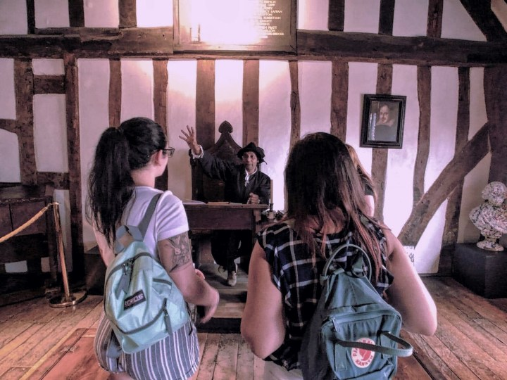 Two women with backpacks stand on line to meet the school master in Shakespeare's school house in Stratford Upon Avon