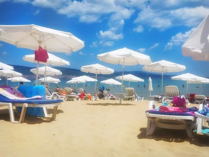 A view of the Black Sea from a beach in Sunny Beach, Bulgaria. There are a bunch of lounge chairs and white umbrellas.