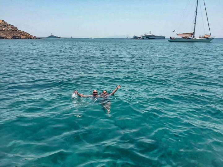 A husband and wife posing for a picture in the sea in Greece. Wife is laughing and falling below water because she got drunk when sailing around Mykonos