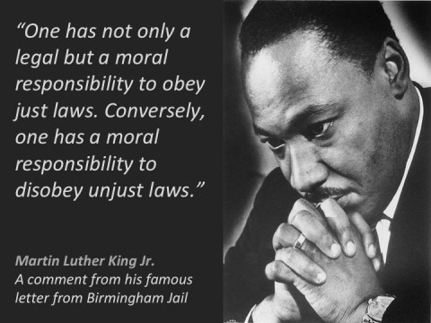 """Portrait of Dr. Martin Luther King Jr., seemingly deep in thought, hands clasped by his face. Quote reads: """"One has not only a legal but a moral responsibility to obey just laws. Conversely, one has a moral responsibility to disobey unjust laws."""""""