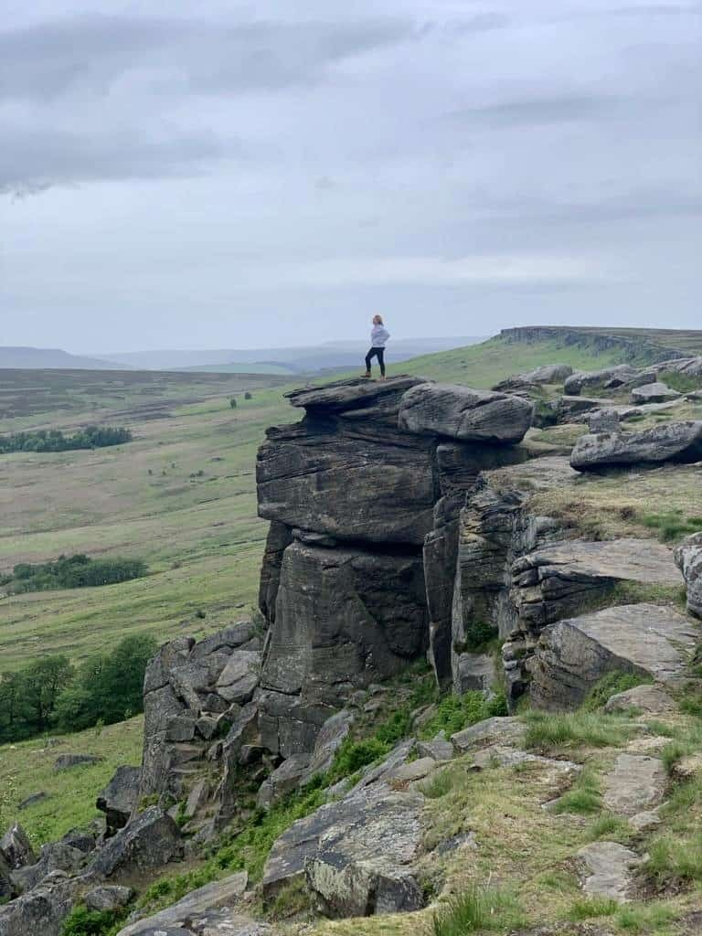 Jen Lowthrop standing on a hill overlooking the Peak District