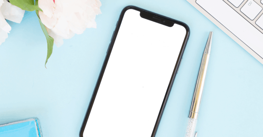 Flat lay of a mobile phone, pen and flowers on a light blue background
