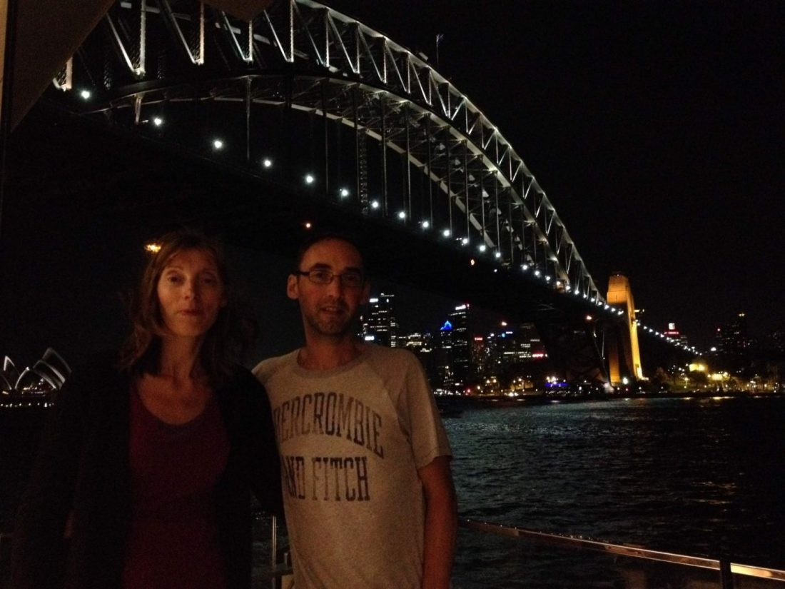 Parents in front of Sydney Harbour Bridge at night