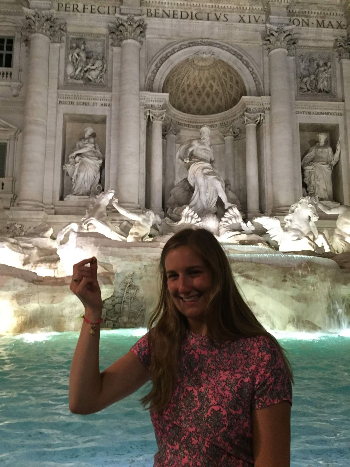Throwing a coin at the Trevi Fountain, Rome