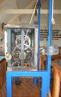 The clockwork mechanism in its original oak frame on a metal supportto allow the weight to drive it in the museum. The small internal cloack face is still attached.