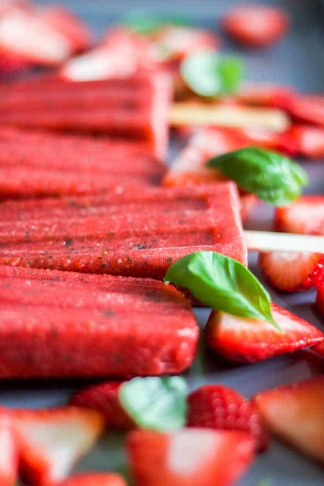 Paleo and healthy three ingredient strawberry basil popsicles! This recipe is easy to make and made with real strawberries, basil and honey. Blend them in your blender and pour in popsicles molds. Freeze for a couple of hours and you have a vegan, paleo and gluten free dessert recipe.