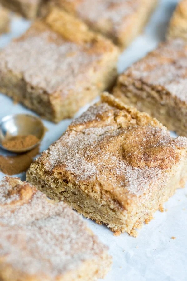 Thick and chewy, these gluten free snickerdoodle blondies are filled with all the flavor and texture you crave from a blondie recipe but don't include any of the gluten. They're filled with butter and brown sugar and lots of cinnamon sugar. This easy recipe doesn't require any mixer and comes together in under 30 minutes. Cut into squares and serve! Keep in the freezer for up to two months.
