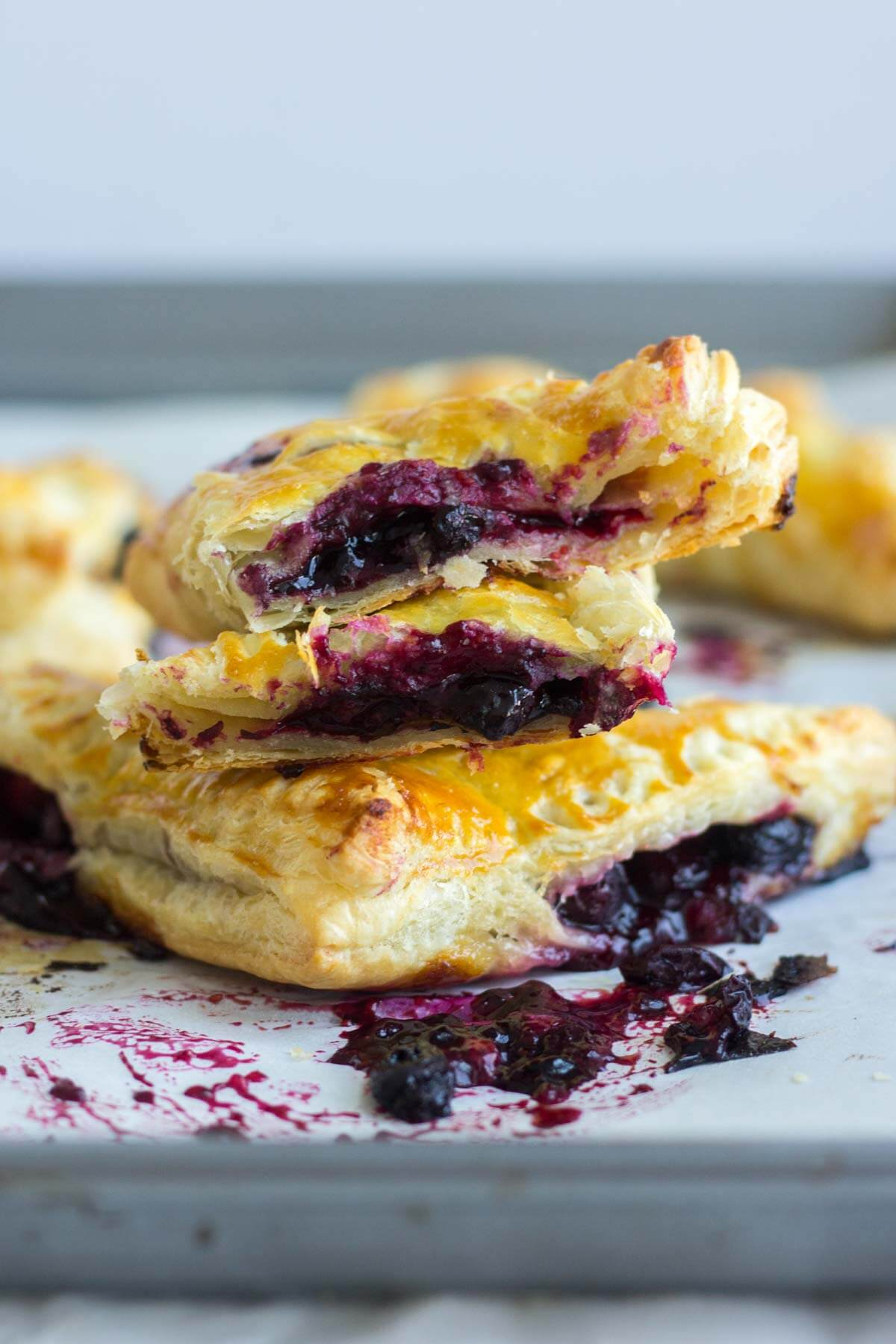 flaky lemon blueberry turnovers stacked on top of each other cut in half