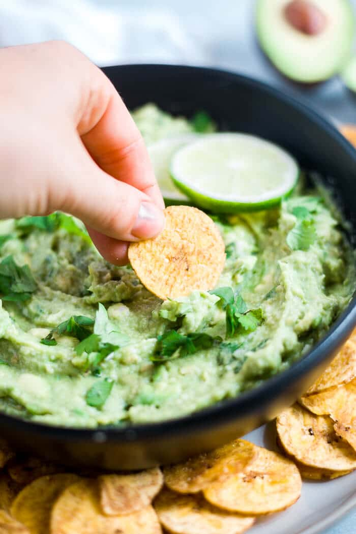 hand dipping into avocado dip with plantain chip