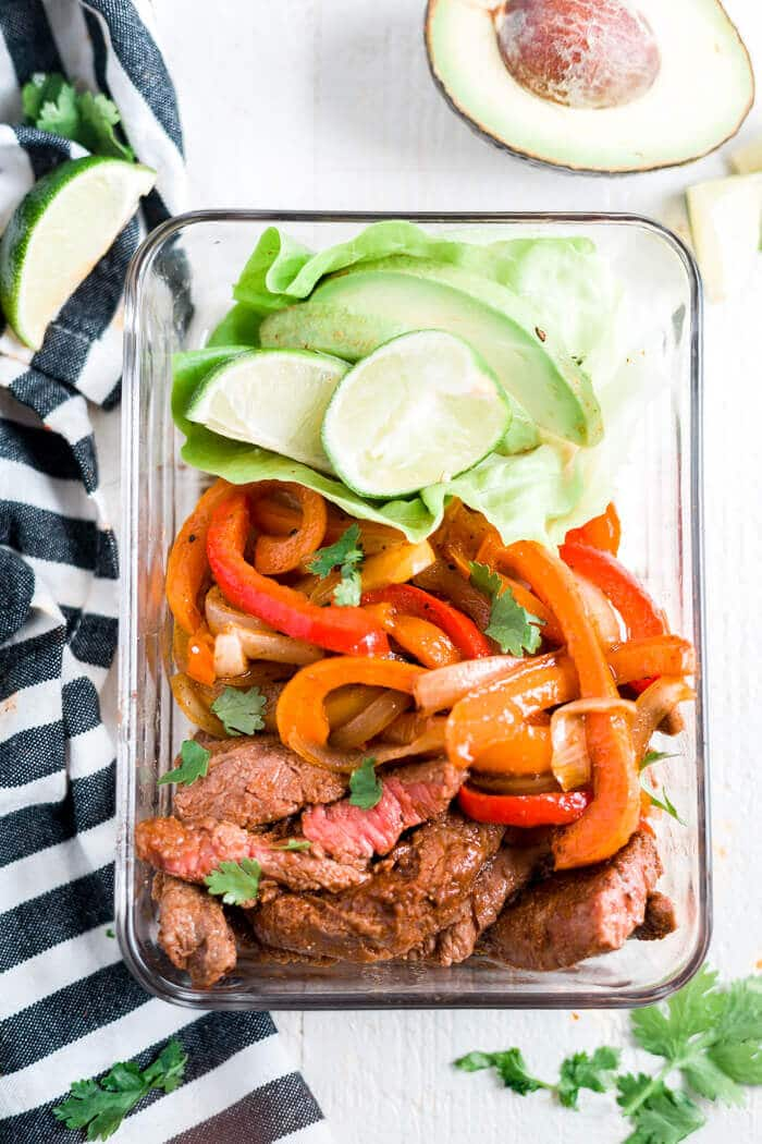 steak fajitas in a glass meal prep container with a side of avocado