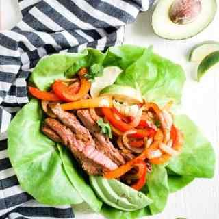 steak fajitas in a lettuce wrap with a lime wedge and half an avocado