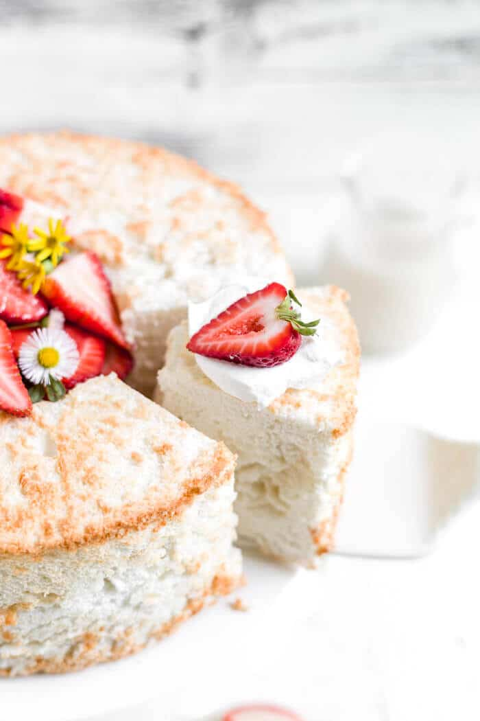 overhead view of a slices of gluten free angel food cake recipe being removed from the cake with a strawberry on top