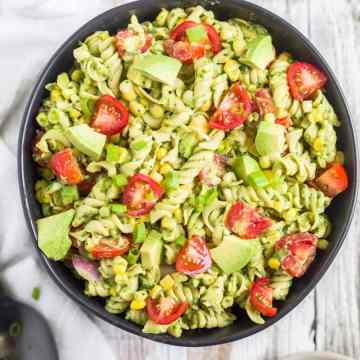 avocado pasta salad in a black bowl