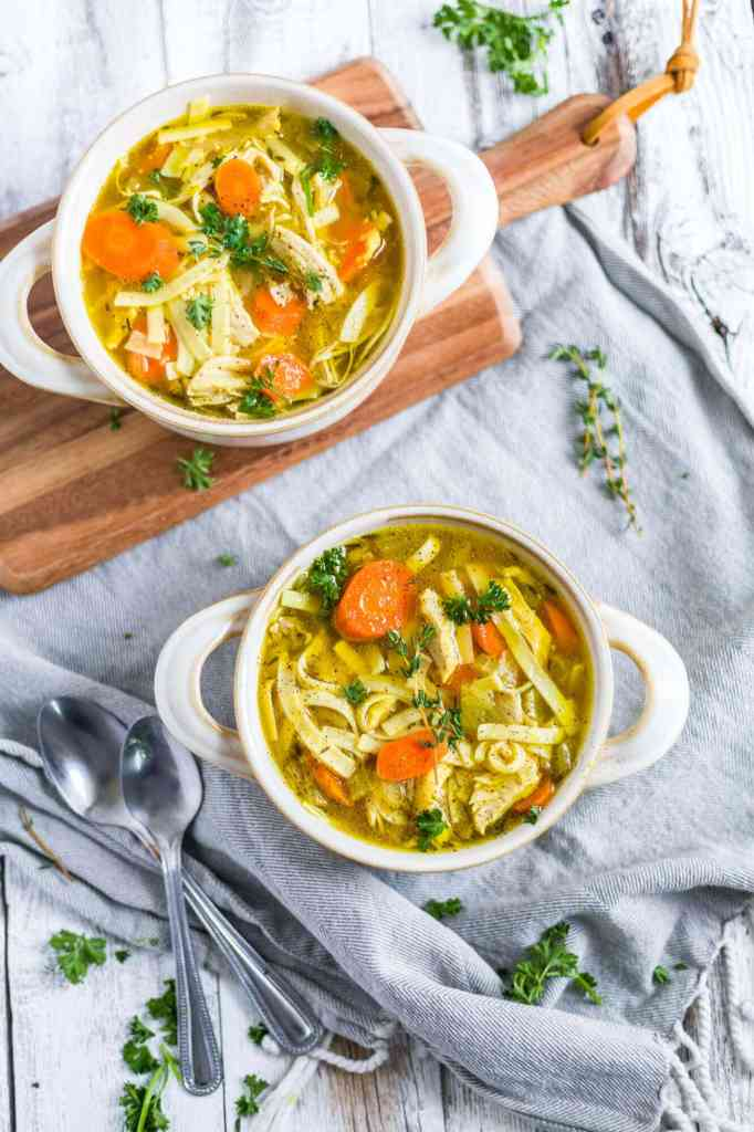 two bowls of chicken noodle soup made in the instant pot with spoons on a cutting board