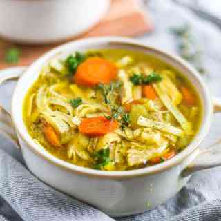 a bowl of instant pot chicken noodle soup recipe with fresh thyme and parsley on top