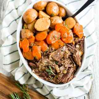 instant pot chuck roast shredded in a bowl with carrots and potatoes