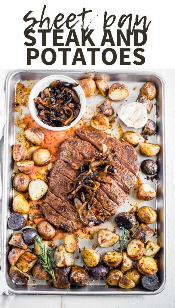 steak and potatoes on a sheet pan with garlic and herbs
