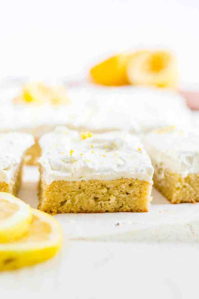 a piece of healthy lemon cake  with dairy free buttercream on a piece of parchment with sliced lemons