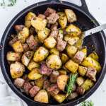 steak bites in a cast iron skillet with a spoon