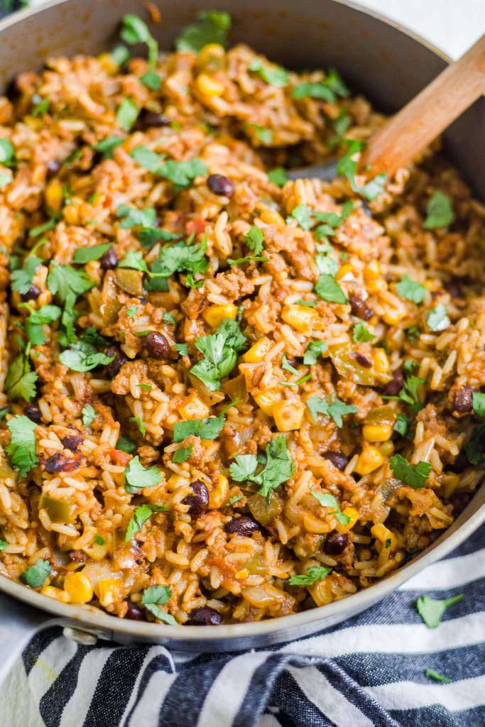 mexican beef and rice in a skillet with a spatula