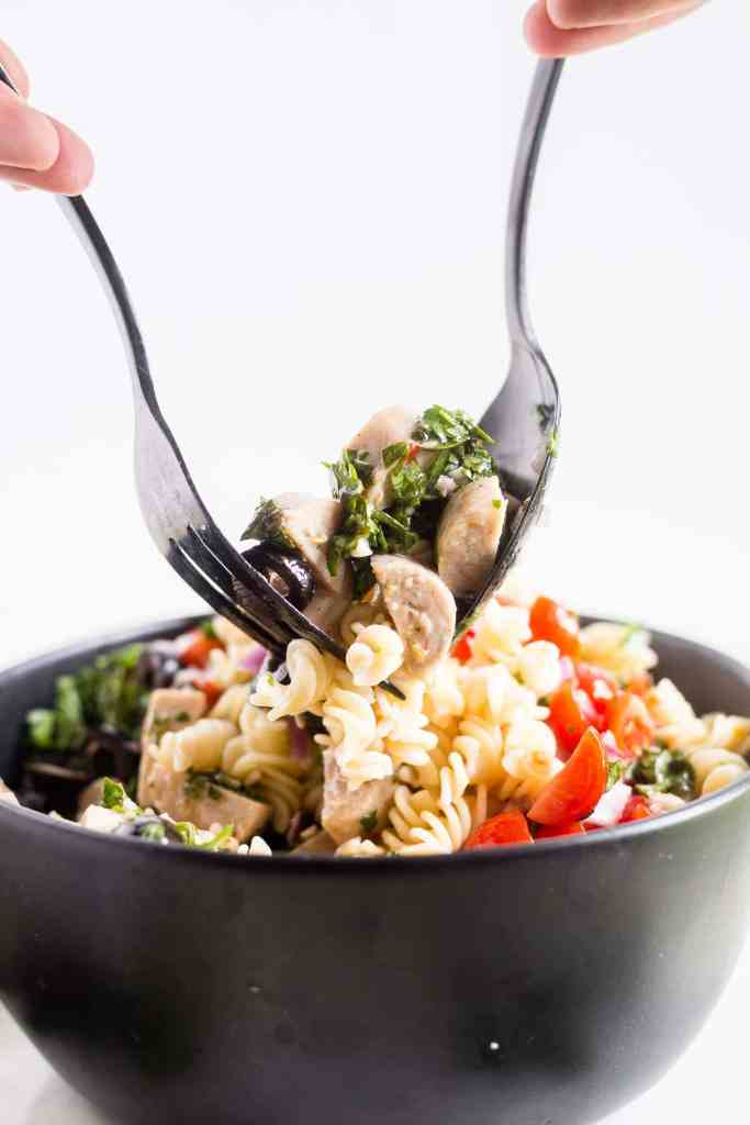 large black fork and spoon mixing Italian pasta salad in a black bowl