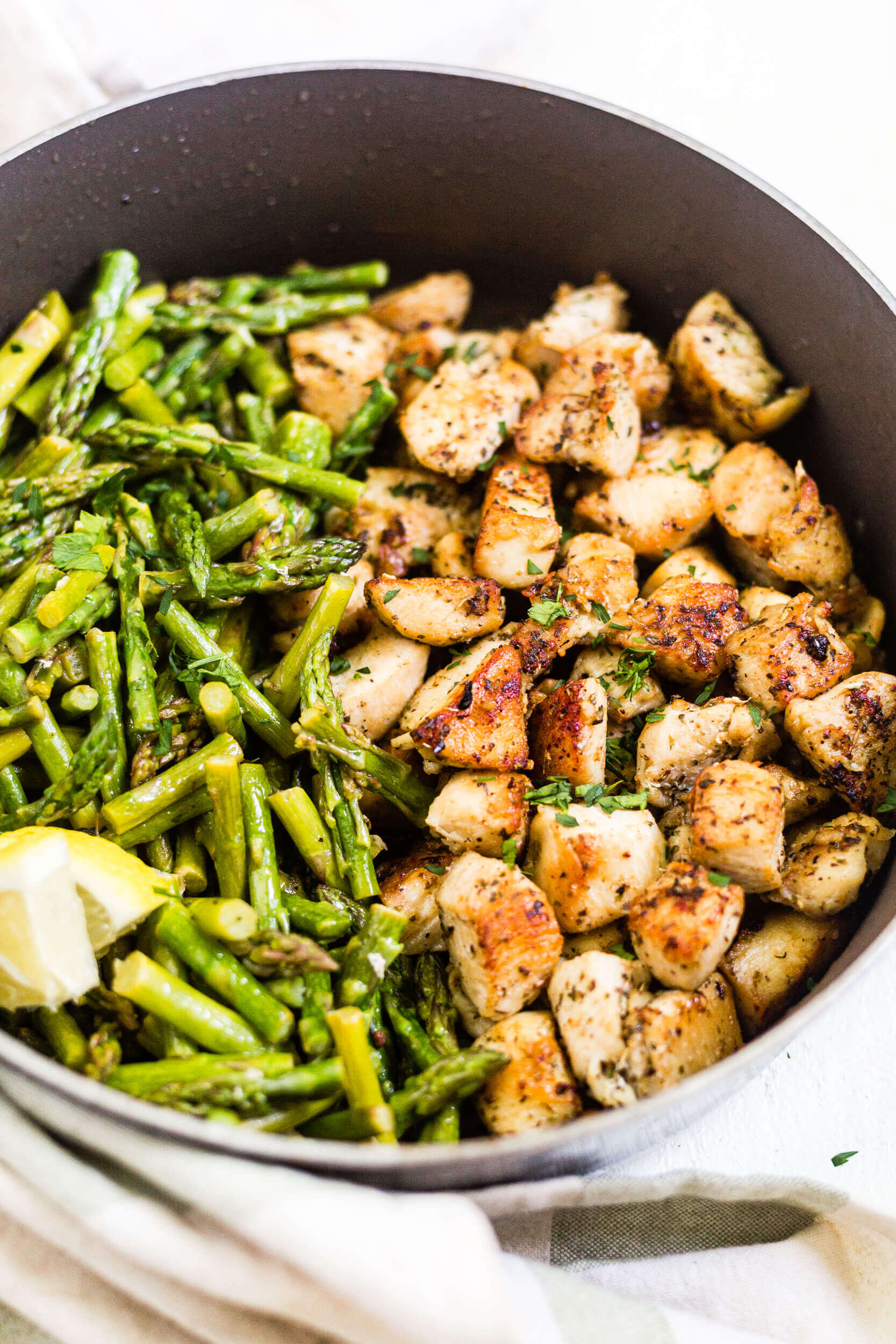 crispy chicken bites in a pan with asparagus
