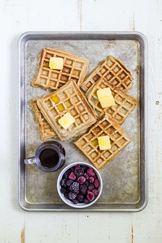 6 gluten free waffles on a sheet pan with syrup and berries