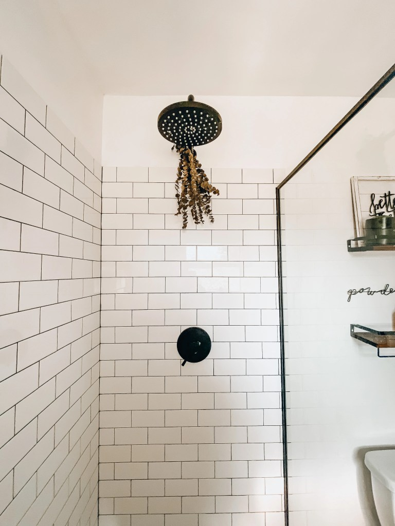 subway tile shower with rain shower head and eucalyptus