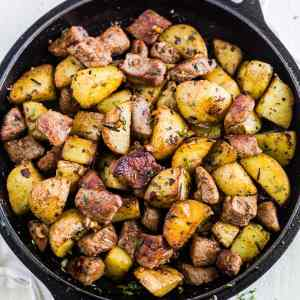 healthy steak dinner with herby garlic steak bites and potatoes in a cast iron skillet