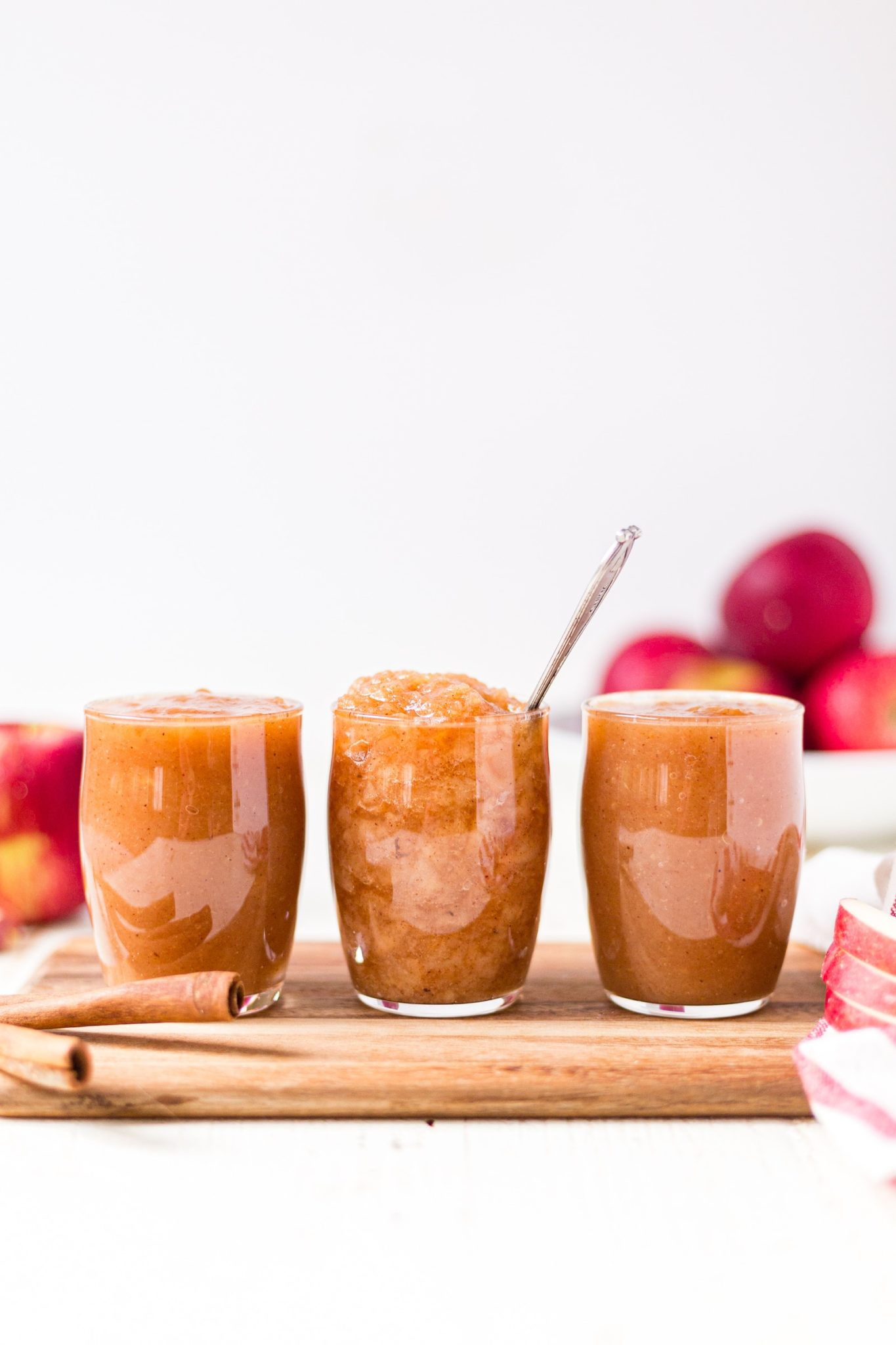 chunky and smooth crockpot applesauce in three jars on a wood cutting board