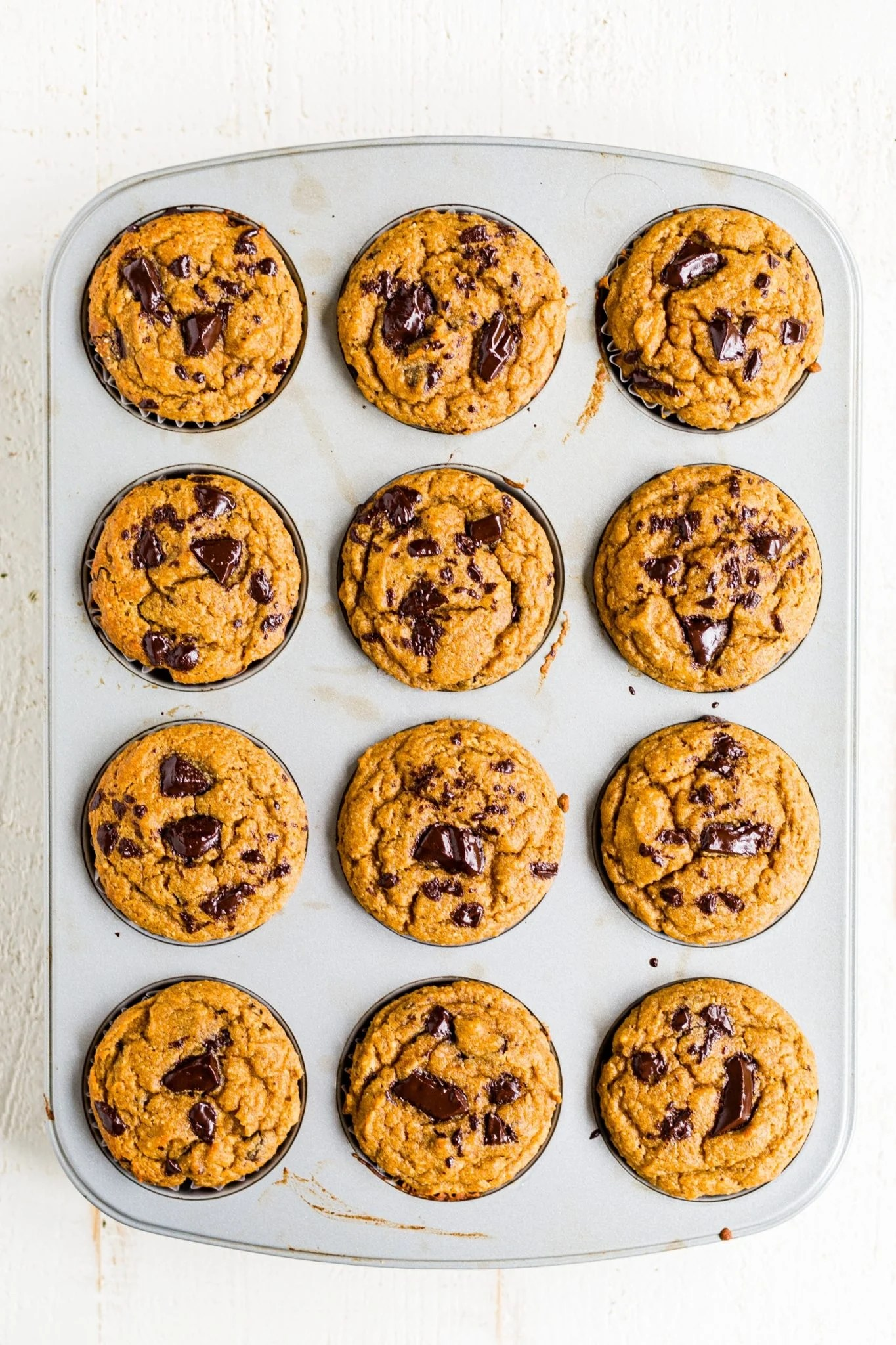 healthy pumpkin chocolate chip muffins in a muffin tin cooling on the table