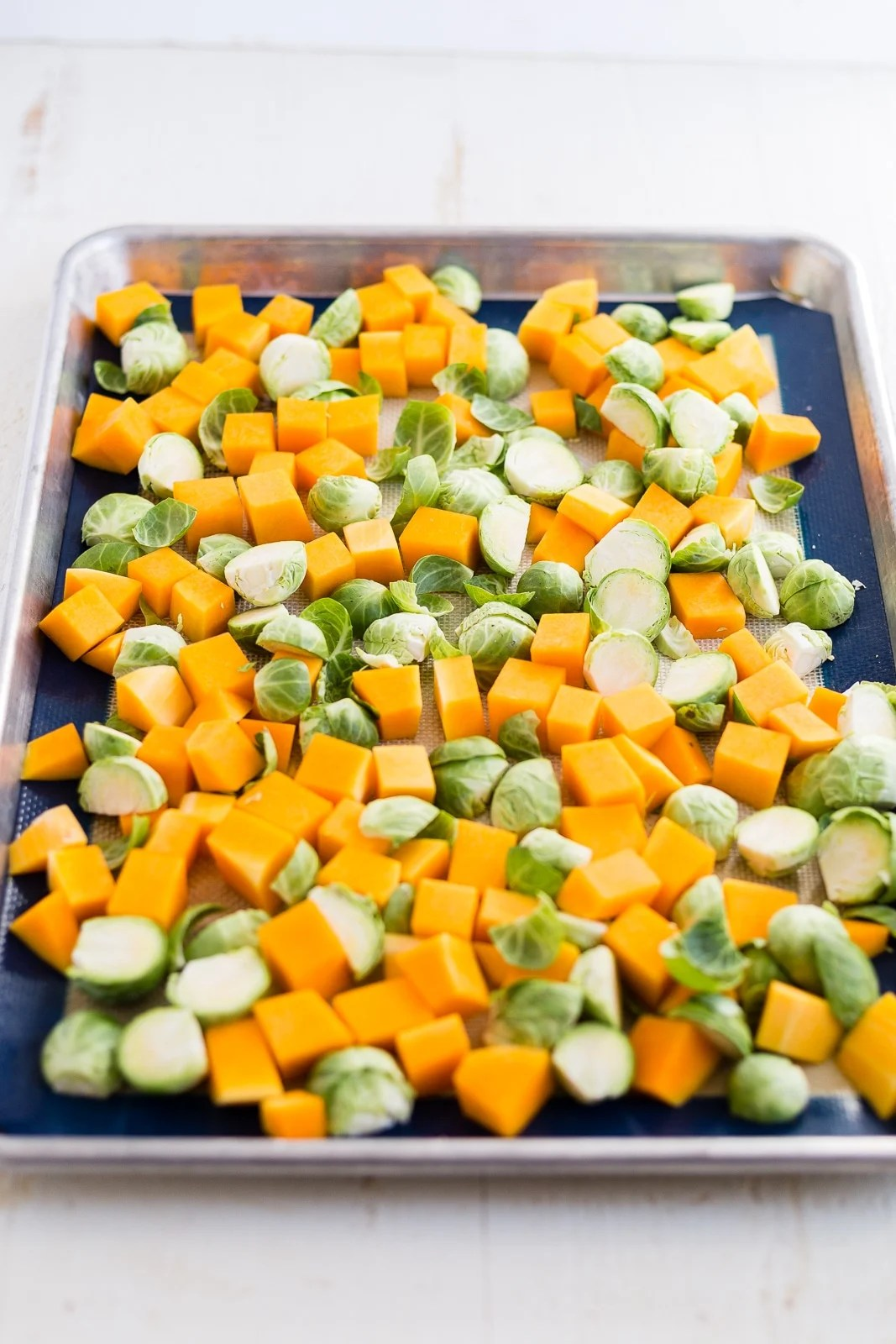 brussel sprouts and butternut squash on a sheet pan before roasting