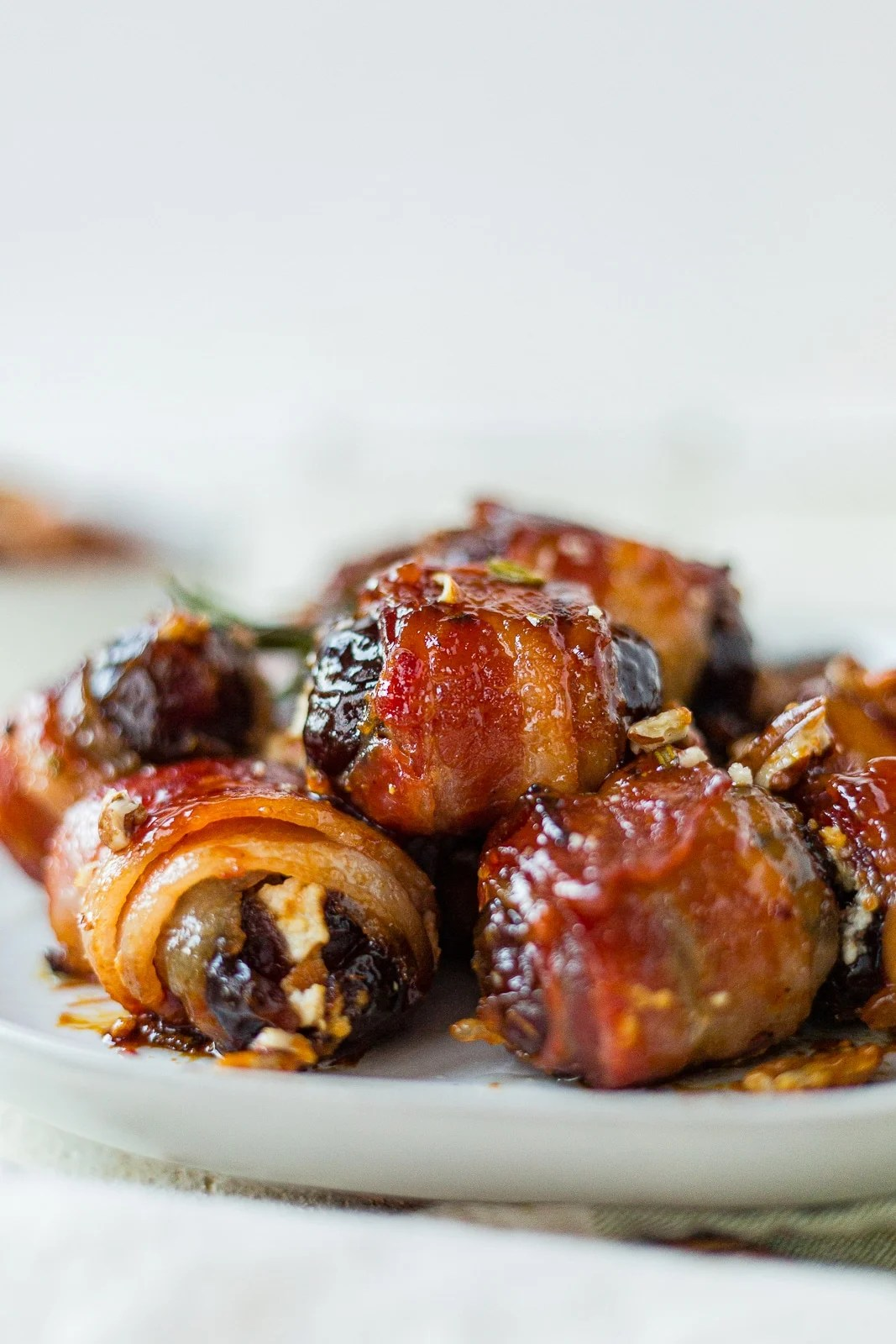 close up of bacon wrapped dates on a white serving platter