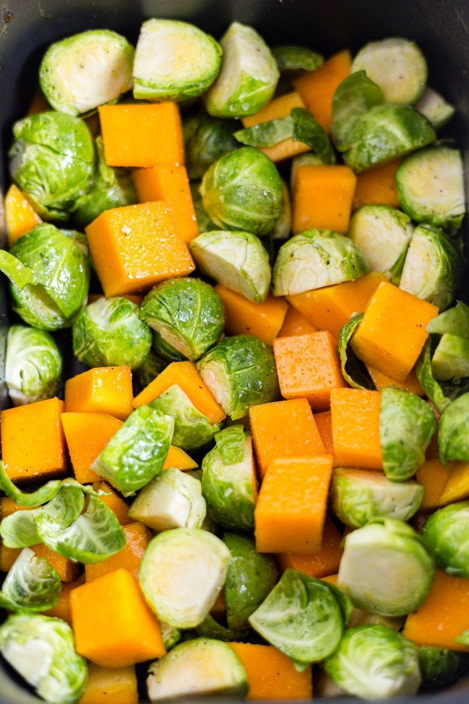 brussel sprouts and butternut squash in an air fryer basket