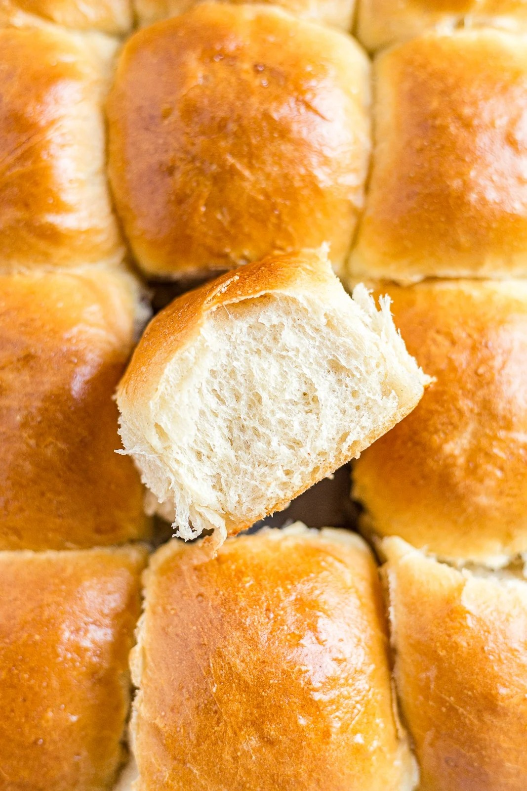 sourdough rolls in a pan with one being pulled out