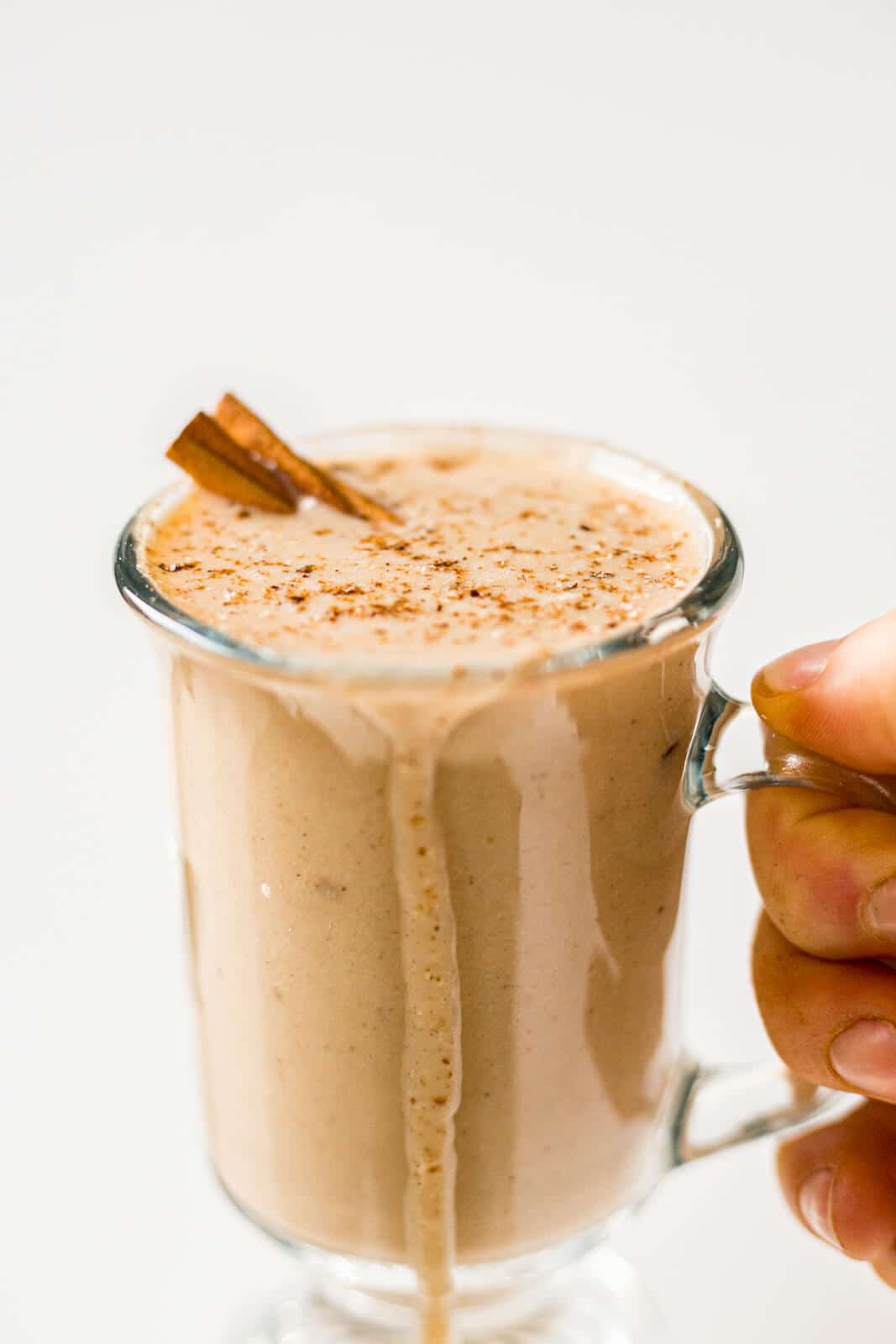 hand holding a glass of dairy free eggnog with it overflowing on the side and topped with fresh nutmeg and a cinnamon stick