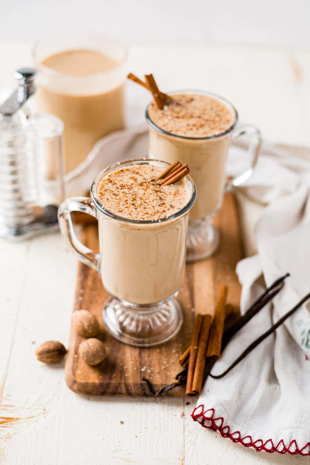 two glasses of dairy free eggnog on a wooden tray with fresh eggnog and cinnamon sticks