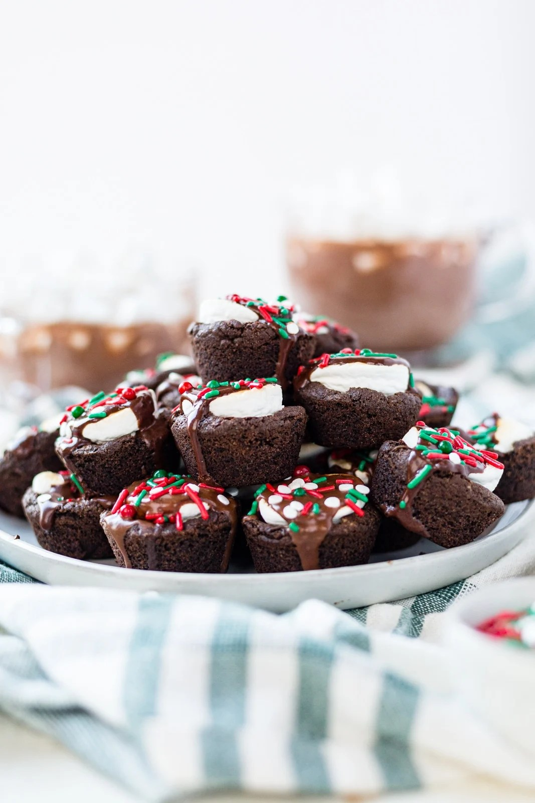 a platter of hot cocoa cookies topped with christmas sprinkles sitting on a green towel with warm hot cocoa in the background